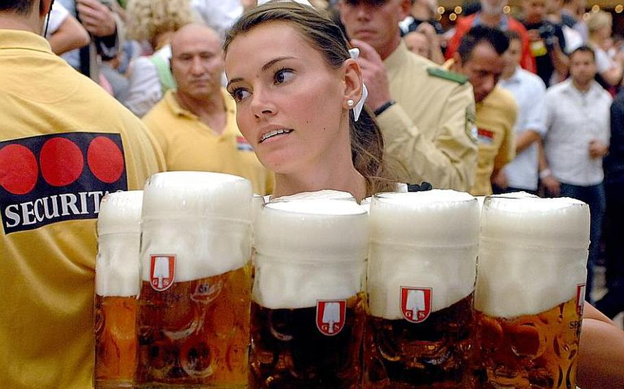 A waitress delivers liter mugs of beer in the Schottenhamel Festhalle on the first day of Oktoberfest in Munich, Saturday.  In years past, revelers have consumed more than 7 million liters of beer.