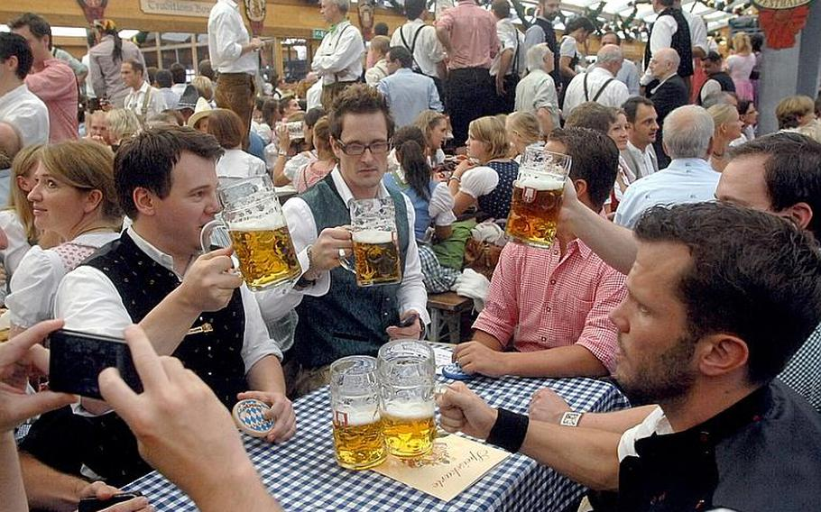 The beer is flowing in the tents on opening day at Oktoberfest in Munich. The festival runs through Oct. 3.