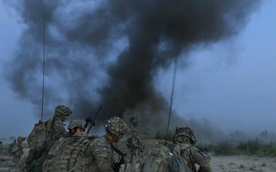 Soldiers with Company C, 1st Battalion, 32 Infantry Regiment, 3rd Brigade Combat Team, 10th Mountain Division move forward after an anti-personnel obstacle breaching system is blown at dawn during Operation Steel Lion III on August 27, 2011, at Strong Point Alizi in Kandahar Province, Afghanistan.