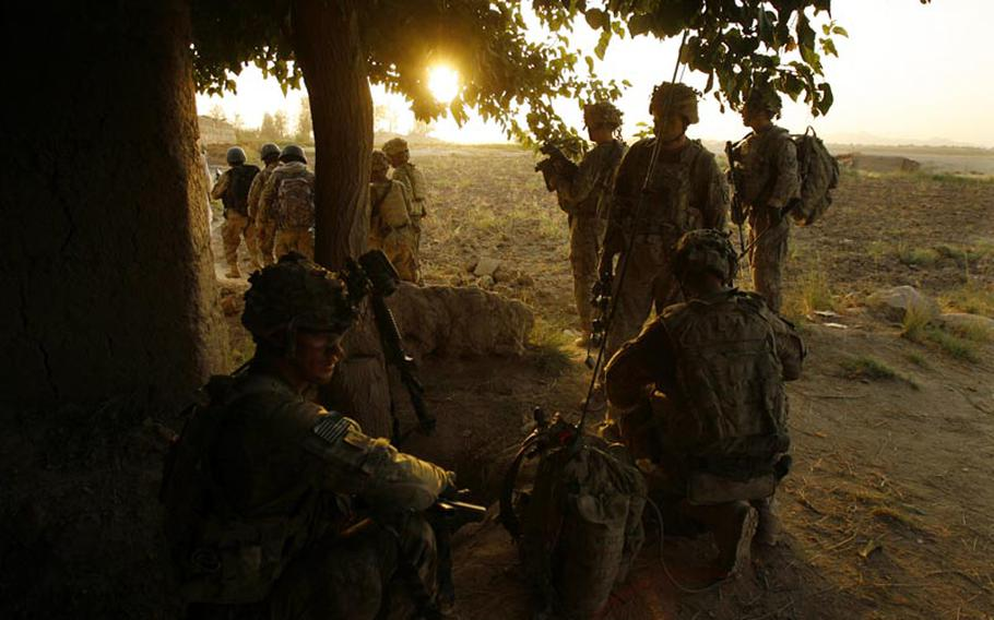 Soldiers with Company C, 1st Battalion, 32 Infantry Regiment, 3rd Brigade Combat Team, 10th Mountain Division pause before pushing into another compound during Operation Steel Lion III on August 27, 2011, at Strong Point Alizi in Kandahar Province, Afghanistan.