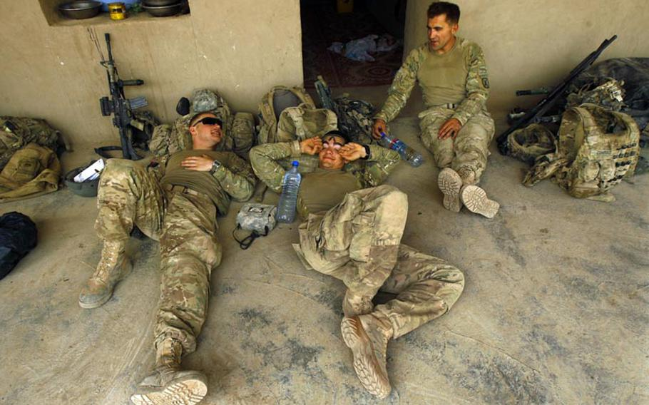 Pfc. Nicholas Seay, left, Pfc Christopher Merendino, and Sgt. 1st Class Carter Conrad all of Company C, 1st Battalion, 32 Infantry Regiment, 3rd Brigade Combat Team, 10th Mountain Division, relax during rest rotation at a compound during Operation Steel Lion III on August 27, 2011, at Strong Point Alizi in Kandahar Province, Afghanistan.