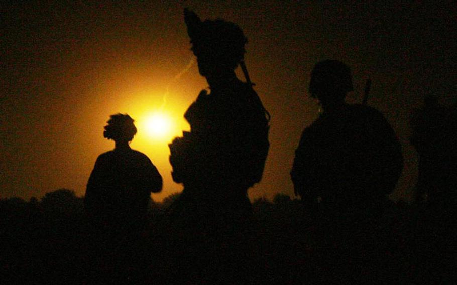 Soldiers with Company C, 1st Battalion, 32 Infantry Regiment, 3rd Brigade Combat Team, 10th Mountain Division are lit up by luminary rounds as they wait for their helicopters during Operation Steel Lion III on August 27, 2011, near Combat Outpost Ahmed Khan in Kandahar Province, Afghanistan.