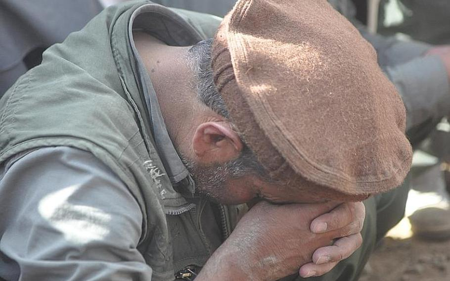 A man grieves at the gravesite of former Afghanistan President Burhanuddin Rabbani, who was buried in Kabul on Sept. 23. A suicide bomber who claimed to represent the Taliban assassinated Rabbani in his home three days earlier.