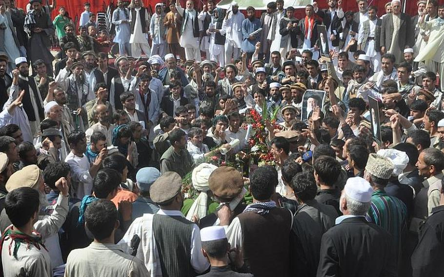 Mourners gather around the grave of former Afghanistan President Burhanuddin Rabbani, who was laid to rest in Kabul on Friday. Thousands of mourners gathered for the burial amid tight security.