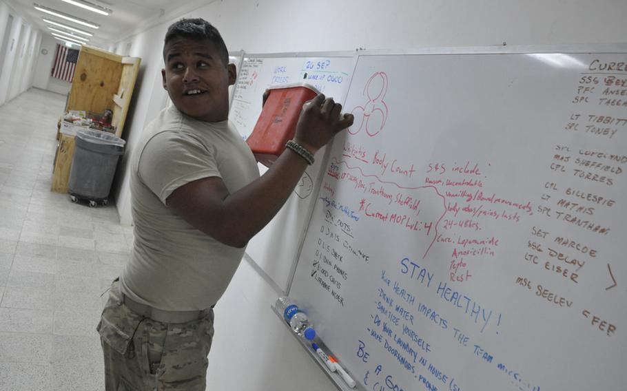 Spc. Steven Miramontes draws a biohazard symbol above the names of soldiers in his unit who've become sick.