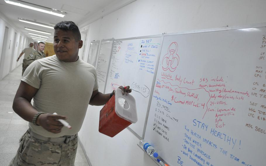 Spc. Steven Miramontesjokes with unitmates after drawing a biohazard symbol above the names of soldiers in his unit who've become sick.