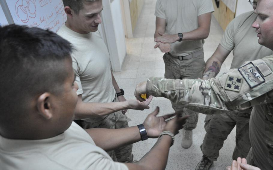 """Spc. Patrick Taggart dispenses hand sanitizer to men in his unit. Several members of this small Security Force Assistance Team have fallen ill in the last week. """"It's funny, as long it's not you,"""" one soldier said."""