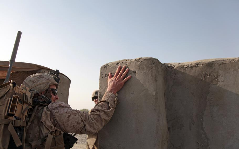 Lance Cpl. Chris Wombaker, a 21-year-old anti-tank assault man from Greenville, Texas, touches a graffito scratched into the cement of the outer wall of Checkpoint 4 in Garmsir district, Helmand province, as he heads out on a patrol with 4th Platoon, Weapons Company, 1st Battalion, 3rd Marines. U.S. casualties fell in September to a five-month low.