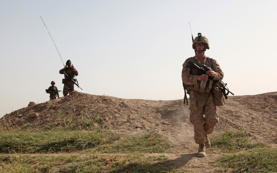 Lance Cpl. Christopher Gray, a rifleman with Company B, 1st Battalion, 3rd Marines, caps a bottle of water during a long patrol in Garmsir district, Helmand province. In September, U.S. casualties in Afghanistan fell to a five-month low.
