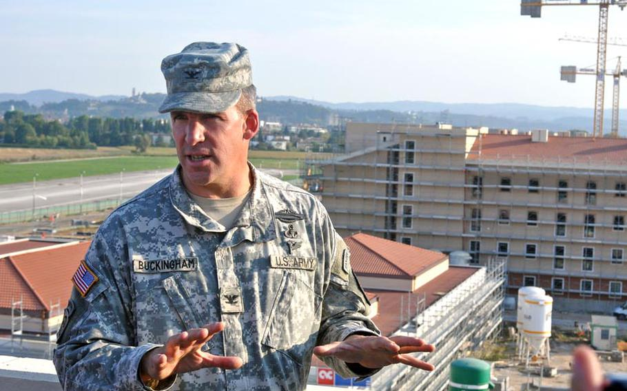 Col. David Buckingham, commander of U.S. Army Garrison-Vicenza, makes a point during a tour of the Dal Molin aifield for Italian civic leaders on Thursday. Behind him to the right is one of the barracks buildings under construction that about 1,200 soldiers will call home when the $289 million project is completed. That's projected to happen in phases in 2013 and 2014.