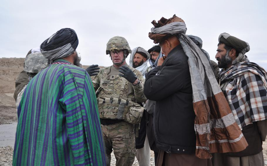 Lt. Col. John O'Grady, commander of 1st Battalion, 84th Field Artillery Regiment, speaks with elders at the opening of a new river crossing near the town of Gormach in western Faryab province.