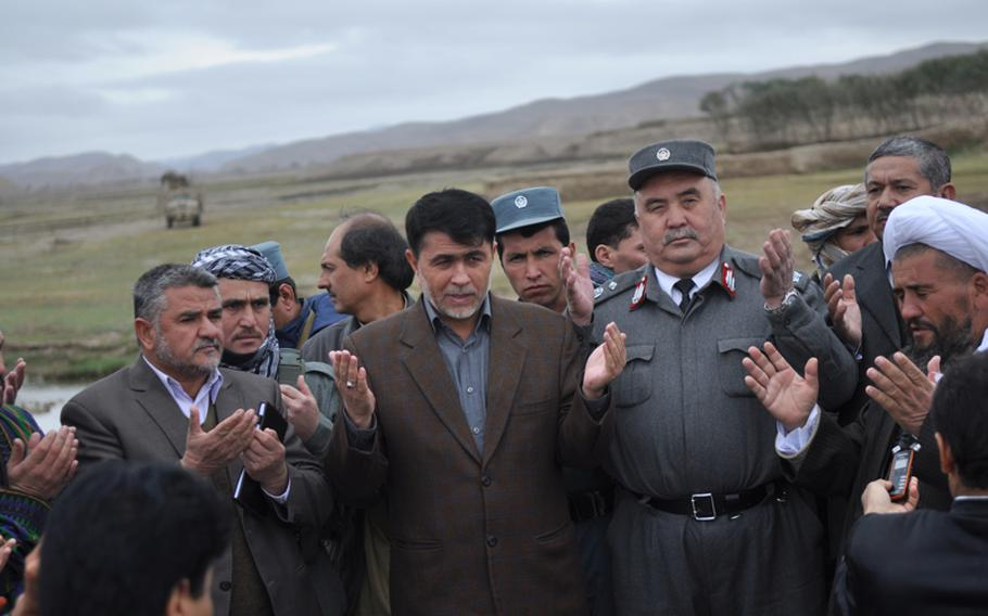 Abdul haq Shafaq, center, governor of Faryab province, offers prayers after a ceremony opening a new river crossing near the village of Gormach in western Faryab Province.