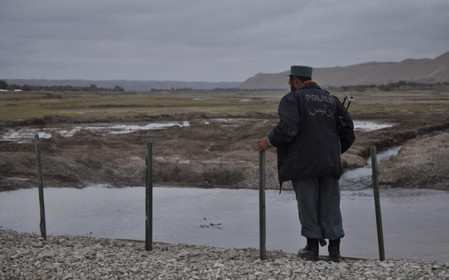 An Afghan National Police officer peers over the edge of a new bridge near the village of Gormach in western Faryab province.