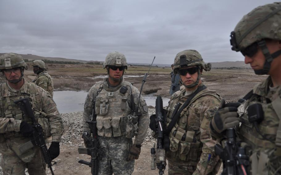 """Capt. Timothy McCarthy second from right, commander of Charlie Battery, 1st Battalion, 84th Field Artillery Regiment, near the town of Gormach in western Faryab province. """"When you get a friend in this area, you gotta latch on with both hands,"""" he said."""