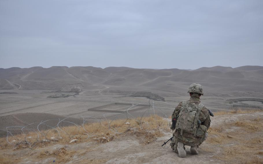 """At a hilltop outpost, American artilleryman looks out over a broad, empty plain in western Faryab. """"This is where ISAF ends,"""" an American officer said."""