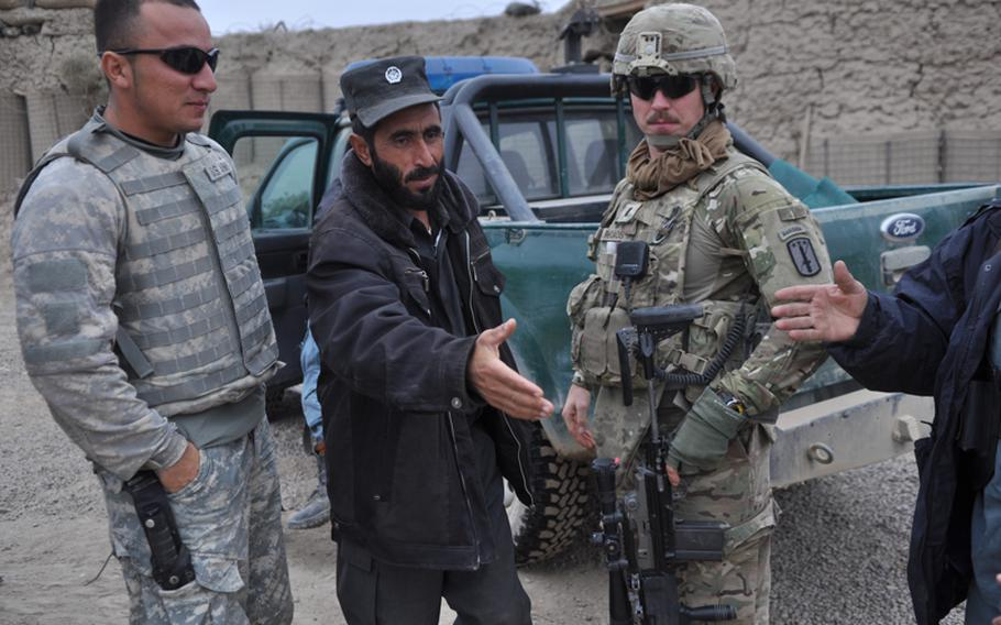 """First Lt. Alexander Rhoads, leader of 3rd Platoon, Charlie Battery, 1-84 Field Artillery Battalion, greets Afghan National Policemen at a checkpoint near the village of Gormach. """"Some of these guys are good and they'll go out on patrols,"""" Rhoads said. """"Some of them never leave their little outposts."""""""