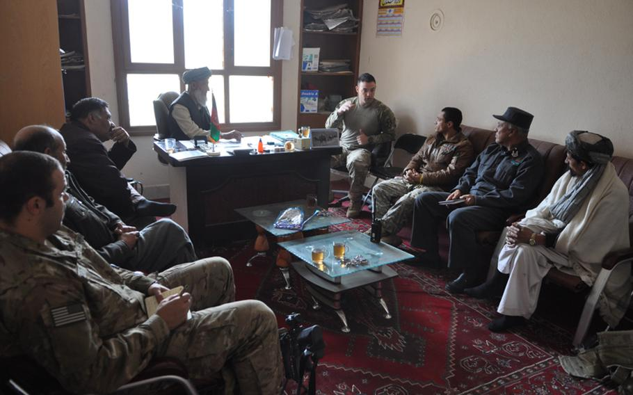 """Capt. Timothy McCarthy, center, commander of Charlie Battery, 1-84 Field Artillery Battalion, talks with Afghan government officials at the district center in Gormach, western Faryab province. """"This place has been described as an economy of force within and economy of force,"""" McCarthy said. """"We are on the fringe."""""""