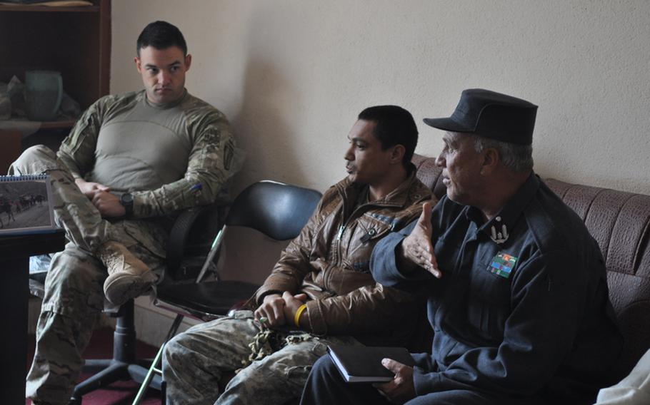 Capt. Timothy McCarthy, left, commander of Charlie Battery, 1-84 Field Artillery Battalion, listens as an Afghan police commander discusses security problems in Gormach, western Faryab province, in November.