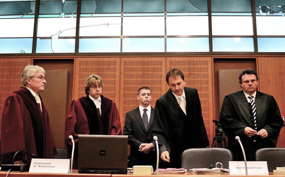 German prosecutors filed the most severe murder charge against Arid Uka, who has admitted to killing two U.S. airmen and trying to kill three more at the Frankfurt International Airport on March 2. Pictured from left are two prosecutors (in red robes), Air Force Staff Sgt. Trevor Brewer, who testified Uka tried to shoot him twice, Marcus Traut, the lawyer representing Brewer and the two wounded airmen, and Marcus Steffel, representing the families of the dead airmen.