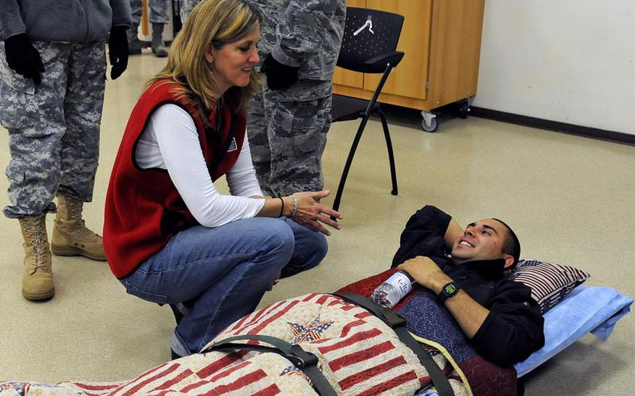 Karolina Wignall, manager for the USO at the 86th Contingency Aeromedical Staging Facility at Ramstein Air Base, talks to Spc. Marcus Ortiz, as he waits for a MEDEVAC flight back to the U.S. Ortiz is resting his head on a donated pillow.
