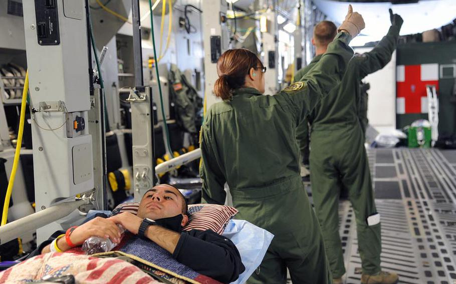 Spc. Marcus Ortiz, waits aboard a C-17 MEDEVAC flight back to the U.S., as crew members give the signal to bring the next stretcher on board. Ortiz is resting his head  on a donated pillow.