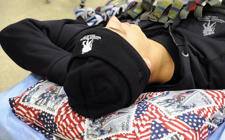 Marine Cpl. Anthony Szekely awaits a MEDEVAC flight back to the U.S. at the 86th Contingency Aeromedical Staging Facility at Ramstein Air Base. His head is resting on a donated pillow.