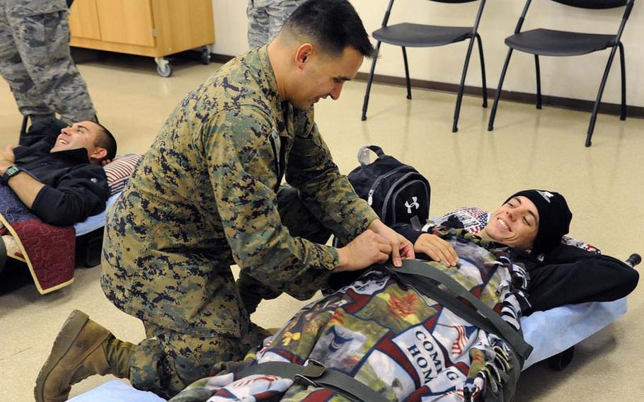 Marine Staff  Sgt. Herbert Dover straps Marine Cpl. Anthony Szekely to a stretcher prior to a MEDEVAC flight back to the U.S. Szekely's head is resting  on a donated pillow.