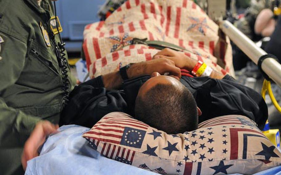 Capt. Donna Eaton makes sure that Spc. Marcus Ortiz is comfortable after being loaded onto a C-17 MEDEVAC flight back to the U.S. Ortiz's head is  on a donated pillow.