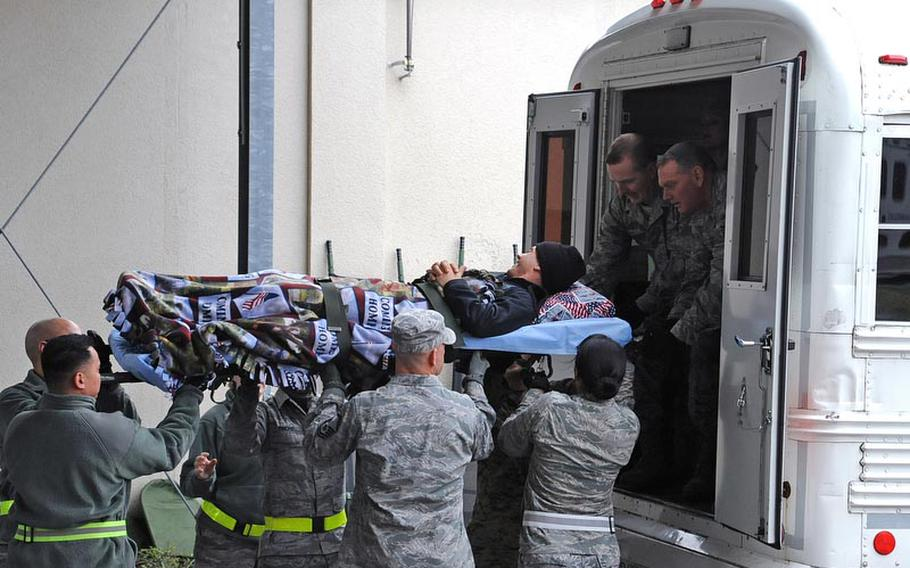 Marine Cpl. Anthony Szekely is loaded on to a bus at the 86th Contingency Aeromedical Staging Facility at Ramstein Air Base for a MEDEVAC flight to the U.S.. His head is resting on a donated pillow.