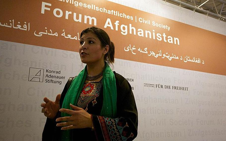 Horia Mosadiq, an Afghan researcher for Amnesty International, speaks with an Afghan journalist Saturday following addresses by German Foreign Minister Guido Westerwelle and Afghan Foreign Minister Zalmay Rasoul at a civil society forum in Bonn, Germany.