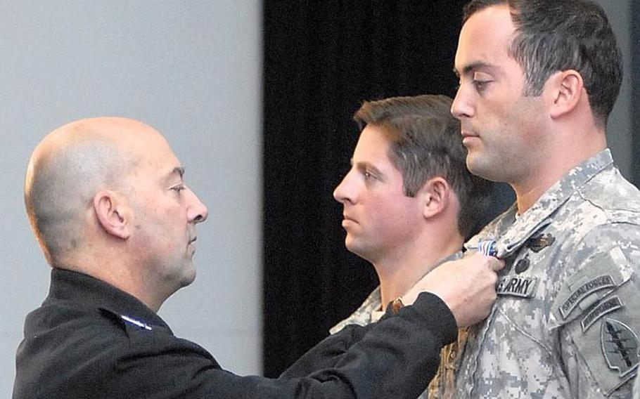 Adm. James Stavridis, head of the U.S. European Command, pins the Silver Star on Sgt. 1st Class McKenna L. Miller during a ceremony Dec. 6, 2011, on Patch Barracks in Stuttgart, Germany. In the background is Army Capt. David G. Fox, who also received the Silver Star. The men received the medal for courage under fire in Afghanistan. A third Silver Star recipient, Staff Sgt. Matthew Gassman, declined to be photographed.