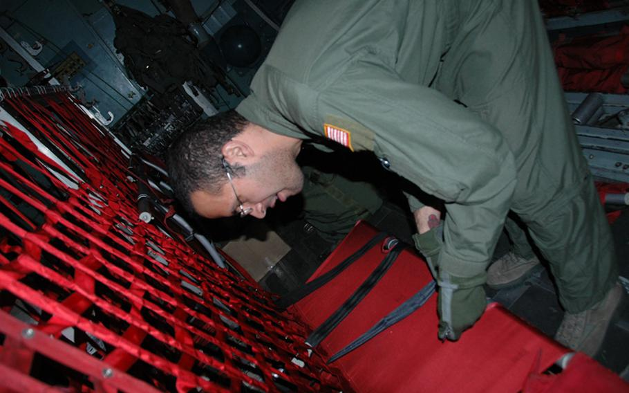 Senior Airman John Quiles, 25, of Runnemede, N.J. prepares a 36th Airlift Squadron C-130 aircraft for Operation Christmas Drop on Thursday.