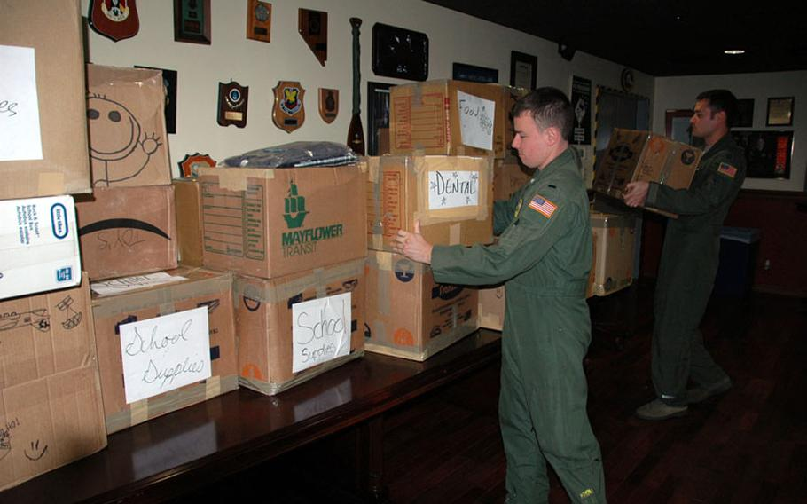 From left: 1st Lt. Weston Fulfer and Capt. Brian Miller of the 36th Airlift Squadron stack aid headed for isolated Pacific islands as part of Operation Christmas Drop at Yokota Air Base on Thursday.