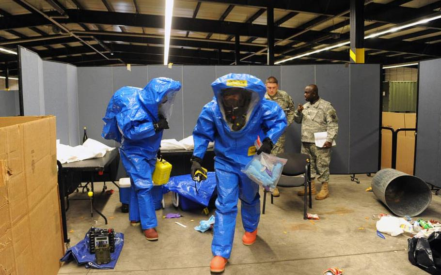 """Sgt. David Larkin, left, and Staff Sgt. Tim Butler, both of the 773rd Civil Support Team, leave the """"contaminated zone"""" during a training exercise in Kaiserslautern on Dec. 6., as Sgt. 1st Class Jose Mora, left, and Staff Sgt. Kwabena Kyeremeh of USAREUR Emergency Management Assessment Team discuss how they did."""