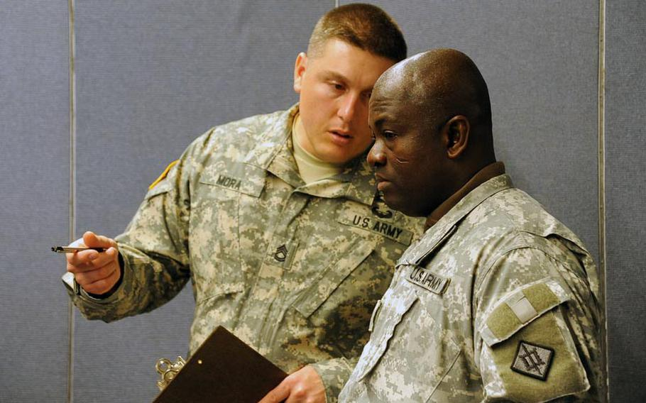 Sgt. 1st Class Jose Mora, left, and Staff Sgt. Kwabena Kyeremeh of U.S. Army Europe Emergency Management Assessment Team discuss how Staff Sgt. Tim Butler and Sgt. David Larkin, both of the 773rd Civil Support Team performed during a HAZMAT exercise in Kaiserslautern, Germany, on Dec. 6.