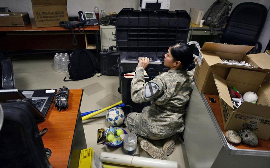 Sgt. Nina Rasa, of 3rd Brigade, 1st Cavalry Division, packs up the remains of her office as she is one of the last soldiers to serve at Camp Adder, Iraq.