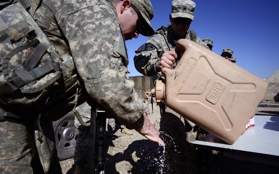 Spc. Tyson Nettles, left, of 1st Battalion,12th Cavalry Regiment, 3rd Brigade, 1st Cavalry Division, washes his hands before eating lunch with the help of Sgt. Cody Street, of the same unit, at Contingency Operating Base Basrah. As facilities shut down in preparation for the withdrawal deadline of Dec. 31, 2011, soldiers are beginning to revert to the way things were done in the early days of the war.