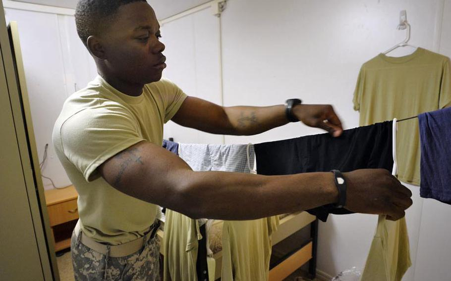 Sgt. Ashanti English, with Alpha Distribution Company, 215th Brigade Support Battalion, 3rd Brigade, 1st Cavalry Division, hangs his clothes in his containerized housing unit after washing them by hand at Contingency Operating Base Basrah. As facilities shut down in preparation for the withdrawal deadline of Dec. 31, 2011, soldiers are beginning to revert to the way things were done in the early days of the war.