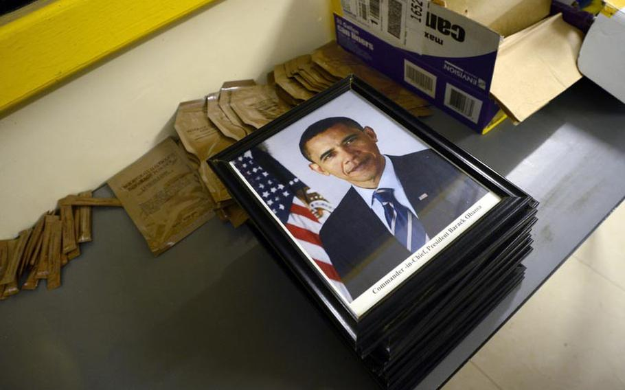 A photo of President Barack Obama sits atop a stack of photos that were taken down from a chain of command display board at Camp Adder, Iraq as the U.S. military prepares to turn the Camp over to the Iraqi government.