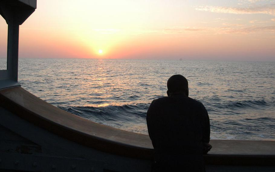 A sailor watches the sun set over the water as the mine countermeasure ship USS Patriot steams towards Kagoshima and annual exercises with the Japanese in late October.