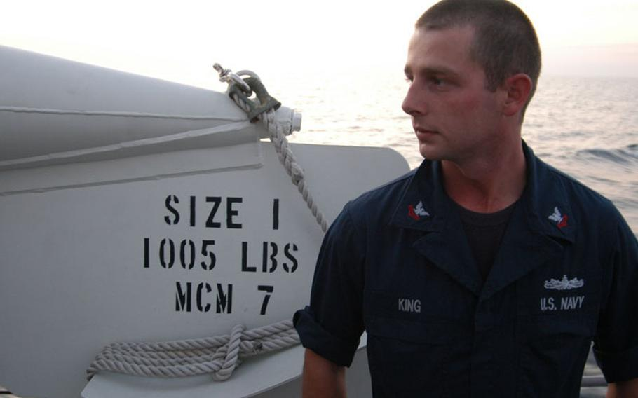 Petty Officer 2nd Class Tyler King stands next to one of mine sweeping floats on the fan tail of the mine countermeasure ship USS Patriot as it heads for Kagoshima and exercises with the Japanese in late October. King is a hybrid sailor, able to perform a myriad of different duties from engine work to prepping the ship's mine neutralization vehicles, which makes him invaluable to a ship with a small crew.
