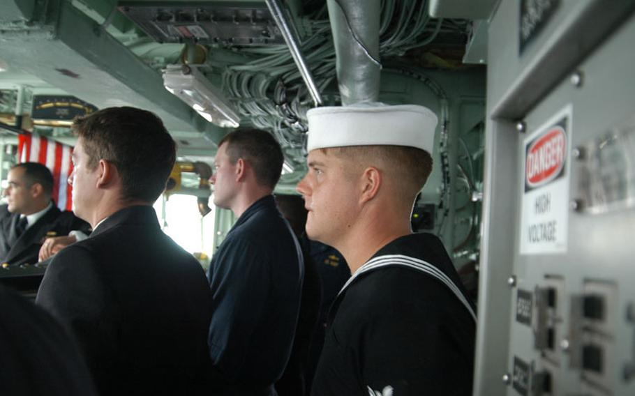Petty Officer 2nd Class Derek Smith of the mine countermeasure ship USS Patriot looks out at Kagoshima's bustling docks from the bridge after helping to lead efforts to tie up and secure the ship after pulling into port in late October, en route to exercises with the Japanese.