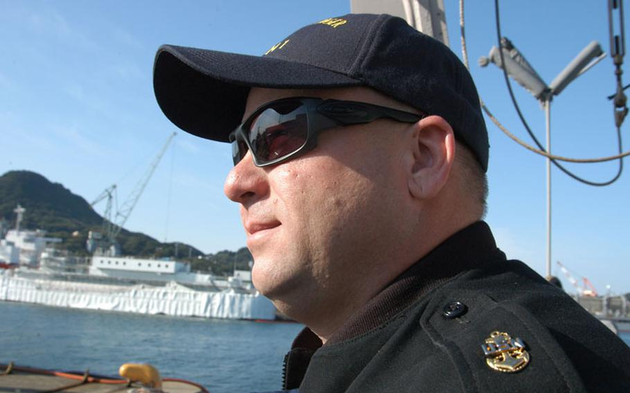 Chief Petty Officer Jeffery Harper of the mine countermesure ship USS Avenger looks out at his home port of Sasebo in November while recounting his involvement aboard a mine ship during the Iraq war in 2003.