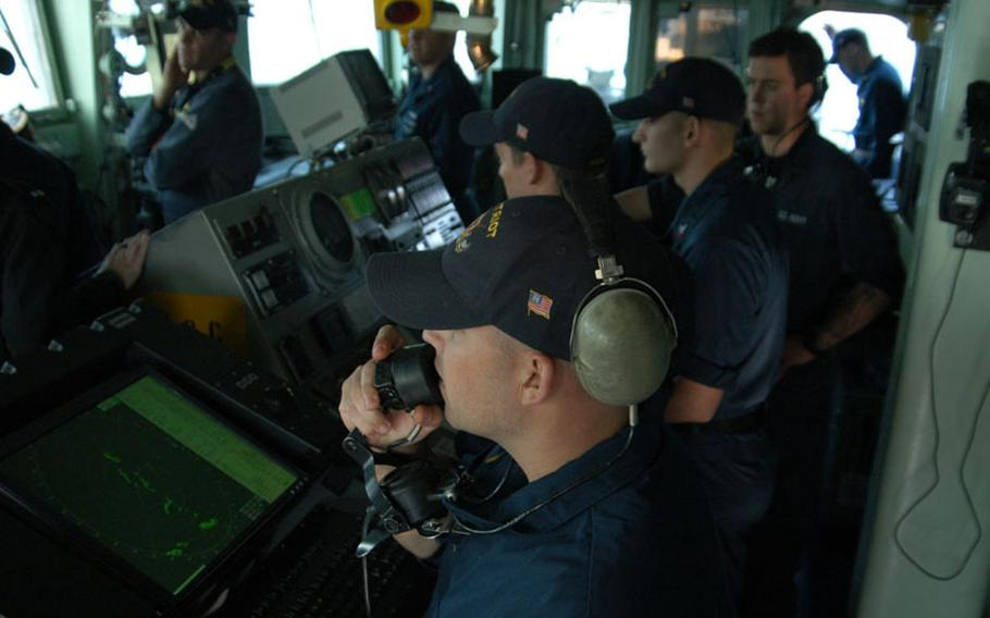 Ensign Andrew Painter of the mine countermeasure ship USS Patriot keeps in contact with his fellow sailors in the combat information center as they watch for potential threats on a late October trip to Kagoshima and annual exercises with the Japanese.