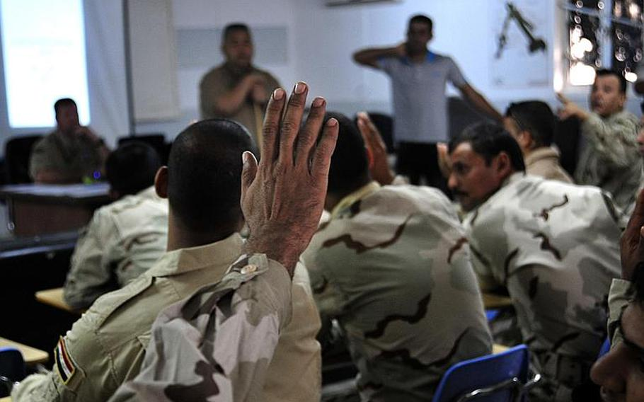 Iraqi Army vehicle maintainers raise their hands Oct. 10 to answer questions during a vehicle maintenance class taught by airmen and contractors in Besmaya, Iraq. The 10-day course focused on engine repair, inspections, and general safety.