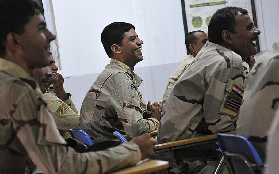 Iraqi Army maintainers laugh at a joke told by their instructor, Vic Martinez, during a vehicle maintenance course in Besmaya, Iraq, Oct. 10. The 10-day course focused on engine repair, inspections, and general safety.