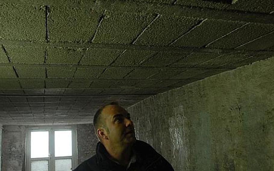 Joerg Rabung, an assistant maintenance manager contractor at Landstuhl Regional Medical Center in Germany, eyes holes in a utility tunnel entry underneath the hospital where part of the ceiling fell out. A ceiling block also fell in an empty pediatric waiting room. Structural engineers say the hospital is safe, but hospital officials say such work orders are a sign of an aging structure that needs to be replaced.