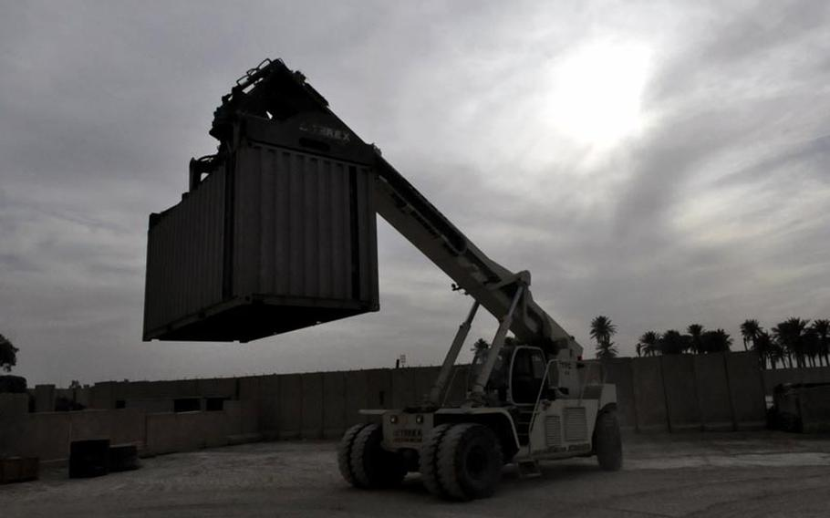 One of the final cargo containers at Camp Echo, Iraq, is moved toward a flatbed Thursday. The base was vacated by all U.S. personnel a few days later.