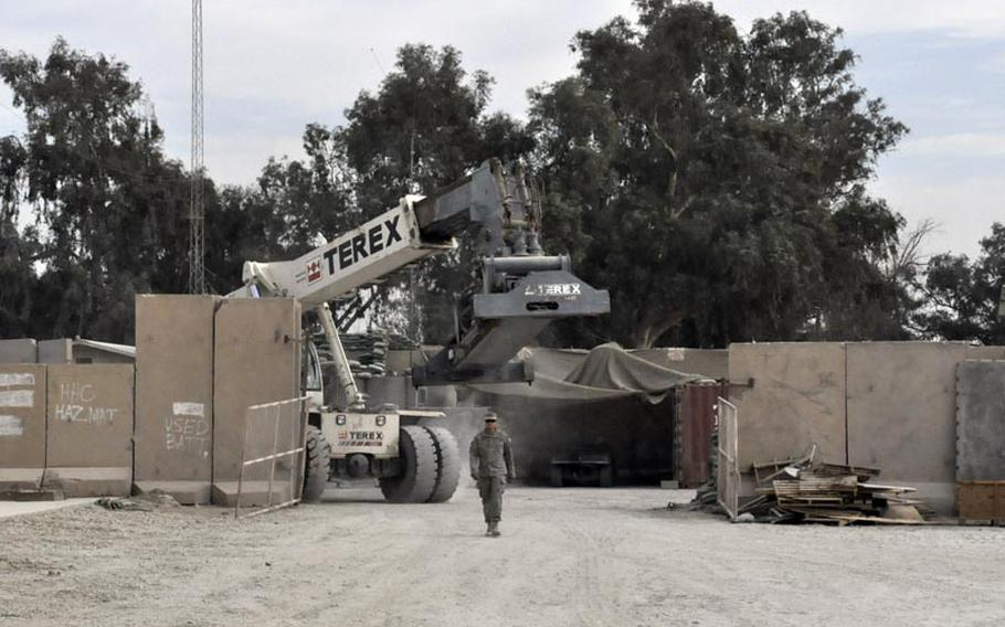 A soldier leads a cargo mover Thursday at Iraq's Camp Echo in anticipation of the base closing later in the week.