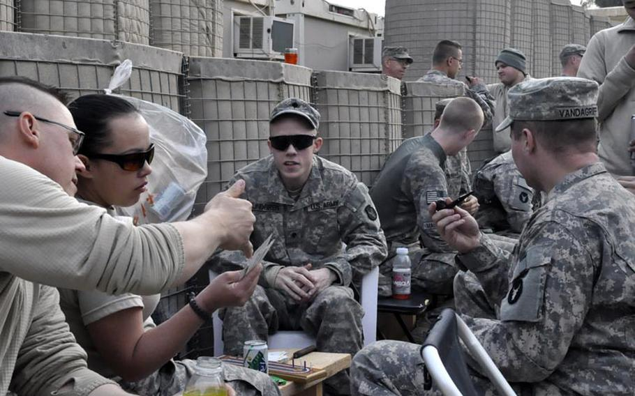 Soldiers with Alpha Company, 1st Combined Arms Battalion, 194th Armor, kick back with a barbecue and some cards Thursday at Camp Echo, Iraq. Since President Barack Obama announced the full withdrawal of U.S. troops from Iraq, the unit has provided security escorts to convoys across the country that are moving materiel down south to Kuwait.
